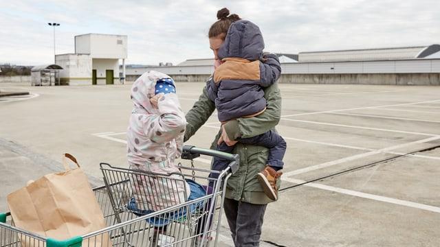Mutter mit zwei Kleinkindern und Einkaufswagen auf leerem Platz