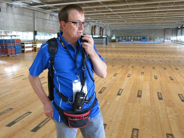 Zu sehen ist Daniel Frutig mit einem Headset und einer Funkanlage.