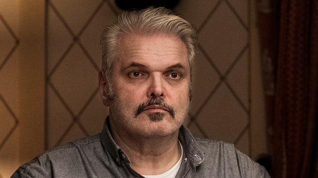 Mann mit blonden Haaren und Schnauz.