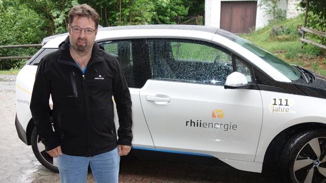 Venanzi Pfister da la Rhiienergie davant in auto electric.