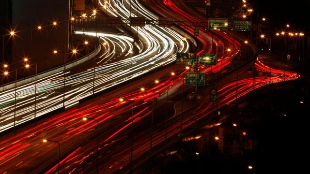 Nachtaufnahme einer Strassse mit Autos, die eine Lichtspur nach sich ziehen.