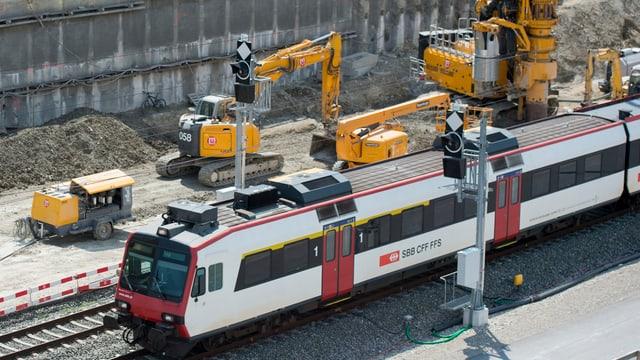 Ein Zug fährt an einer Baustelle vorbei. IM Hintergrund sind gelbe Baustellen-Fahrzeuge zu sehen.