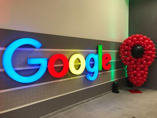 Das Google-Logo vor einer grauen Wand im Treppenhaus.