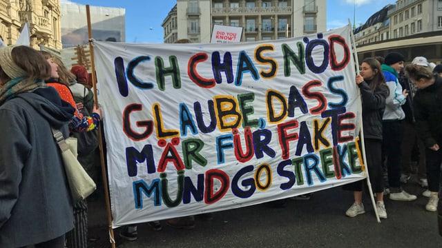 """Schüler halten ein Transparent mit der Aufschrift: """"Ich cha nöd glaube, dass mir für Fakte müend go streike."""""""