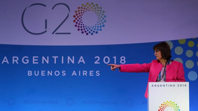 Frau zeigt nach links, im Hintergrund G20-Schild