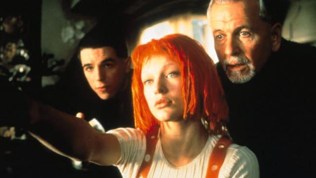 Eine Frau mit orangem Haar zielt mit einer Waffe. Dahinter stehen zwei weitere Männer.