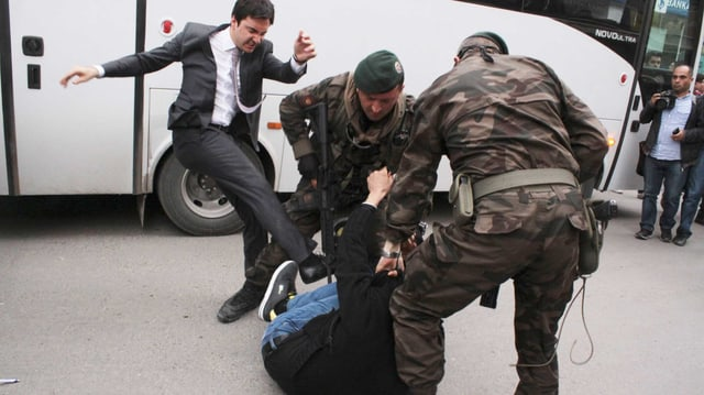 Yerkel schlägt kraftvoll gegen einen am Boden liegenden Demonstranten.