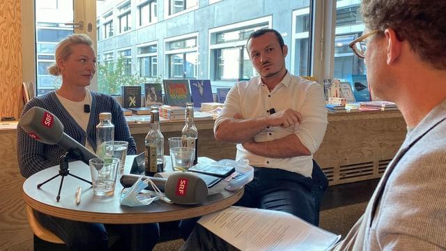 Ein Mann sitzt einem Mann und einer Frau in einem Cafe gegenüber.