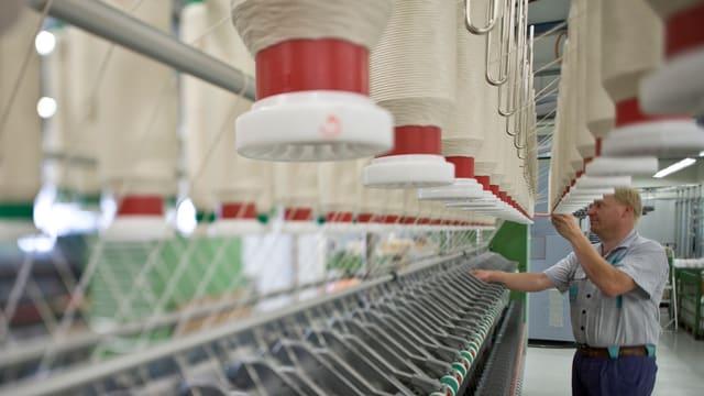 Ein Arbeiter von Rieter in Winterthur kontrolliert die Spindeln an einer Textilmaschine.