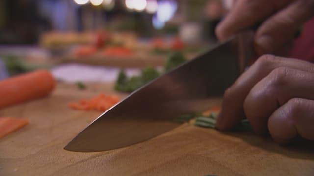 Mann schneidet Petersilie mit einem Kochmesser.