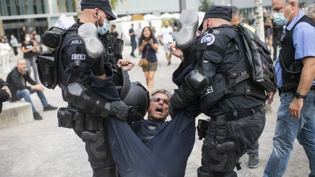 Zu sehen Polizisten, die einen Demonstranten wegtragen.