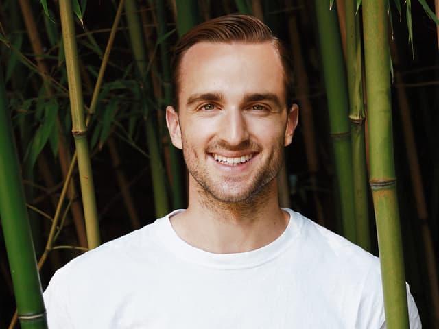 Julian Thorner steht zwischen Bambusstangen.