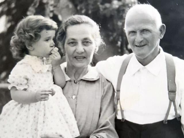 Ein kleines Mädchen auf dem Arm ihrer Grossmutter, daneben steht der Grossvater.