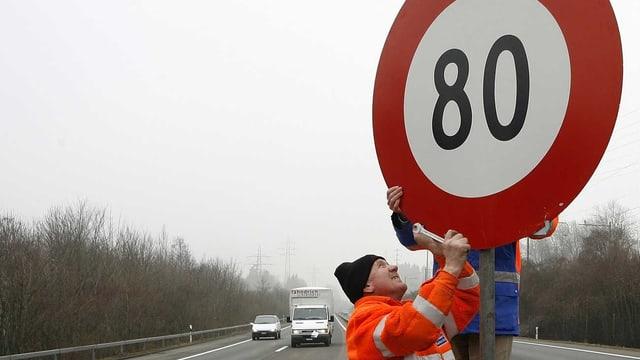 Arbeiter montieren auf einer Autobahn ein Tempo-80-Schild. (keystone)