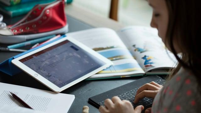 Ein Schülerin macht ihre Hausaufgaben mit Tablet und Schulbuch.