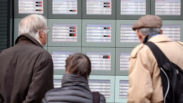 Passanten betrachten Börsenkurse in einem Bank-Schaufenster