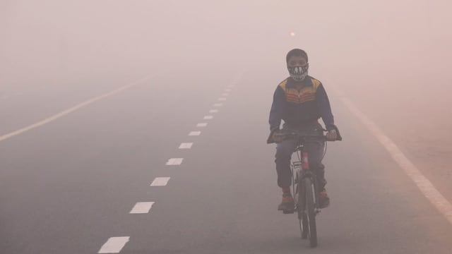 Kind mit Atemmaske auf dem Fahrrad