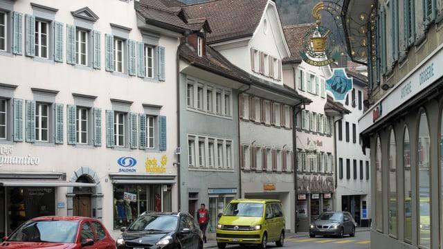 Eine Strasse mit Autos die durch ein Dorf führt, mit alten Häusern rechts und links.