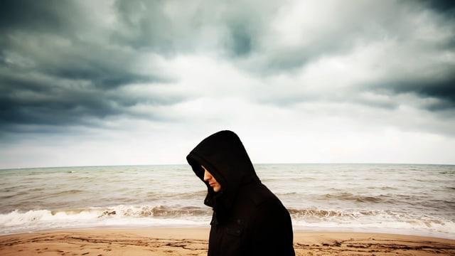 Ein junger Mann mit schwarzem Pullover und Kapuze läuft an einem Strand, hinter ihm das Meer und ein grauer Himmel.