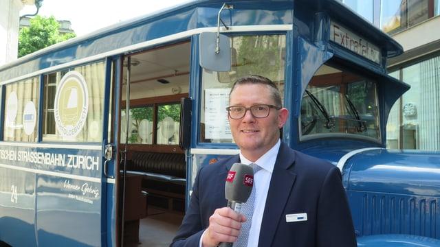 Ein Mann mit Mikrofon steht vor einem blauen, alten Bus