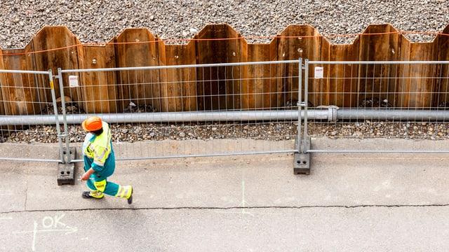 Ein Baustellenarbeiter geht einer Abschrankung aus Eisengittern entlag, Perspektive von oben.