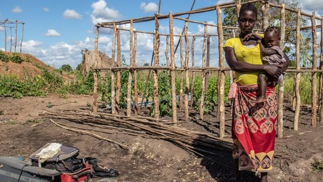 Frau mit Tochter steht vor einem Holzgewächshaus für Pflanzen.