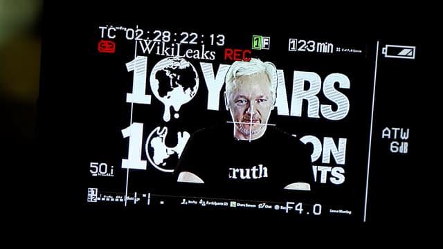 Julian Assange auf einem Foto von der Leinwand. Er trägt ein T-Shirt mit der Aufschrift «truth».
