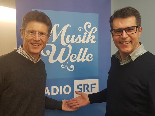 Zwei Männer in schwarzen Pullovern vor Musikwelle-Logo.