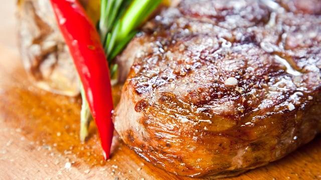 Saftig gebratenes Steak auf einem Holzbrett.