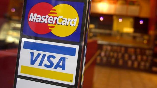 Aufkleber von Visa und Mastercard am Eingang eines Geschäftes