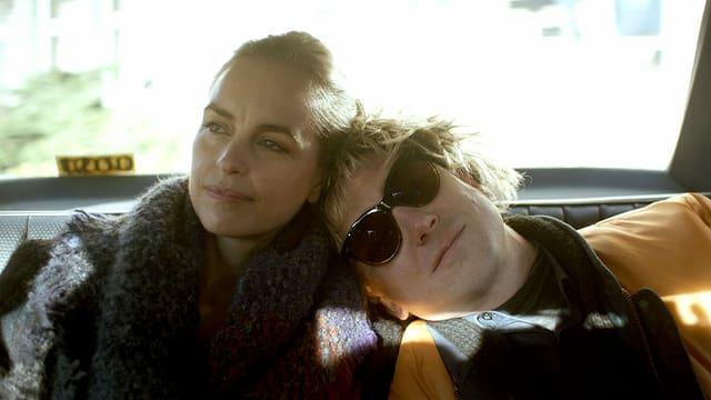 Eine Mann und eine Frau in einem Wagen, er lehnt seinen Kopf gegen ihre Schulter.