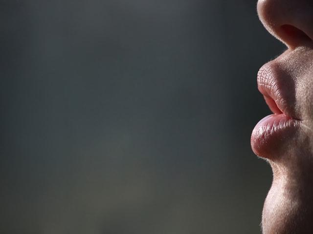 Zoom auf gespitzte Lippen im Profil.