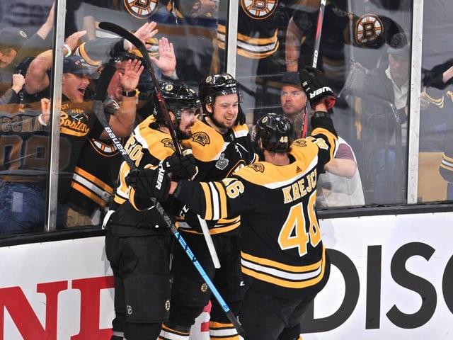 Drei Spieler der Boston Bruins jubeln an der Bande.