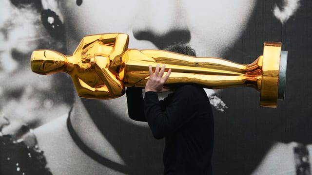 Mann trägt Oscar-Statue.