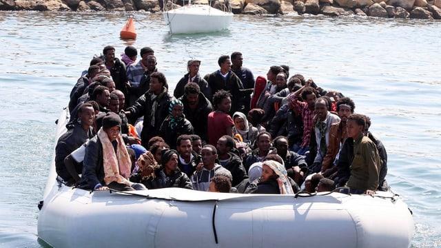 Ein grosses Schlauchboot mit Dutzenden Afrikanern an Bord legt von der libyschen Küste ab.