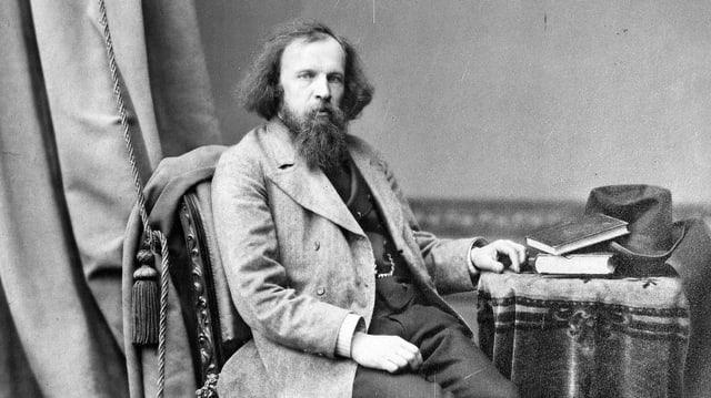 Altes Schwarzweissfoto: Ein Mann mit Bart sitzt auf einem Stuhl