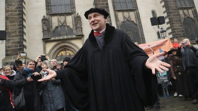 Stadtrat Bernhard Neumann begrüsst die Besucher vor der Schlosskirche in Wittenberg im Martin-Luther-Kostüm.