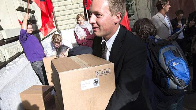Nationalrat Lukas Reimann schleppt Kartonschachteln in die Bundeskanzlei.