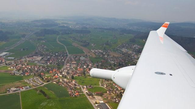 Ein Flügel eines Kleinflugzeugs, darunter eine Siedlung im Mittelland