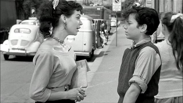 Eine Frau spricht mit einem Jungen auf der Strasse.