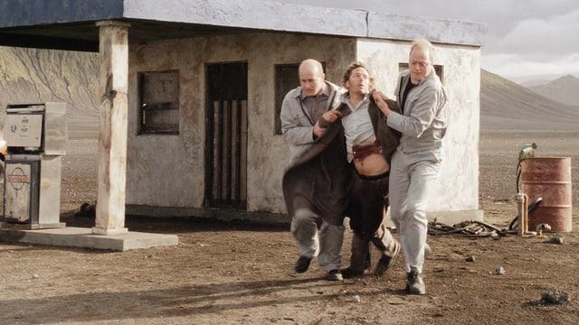 Ein Mann wird von zwei anderen Männern von einer Tankstelle in einer kargen Landschaft gewaltsam weggetragen