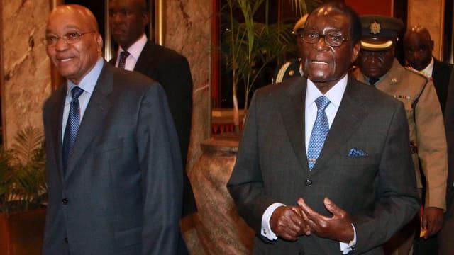 Südafrikas Präsident Zuma geht neben Simbabwes Präsident Mugabe.