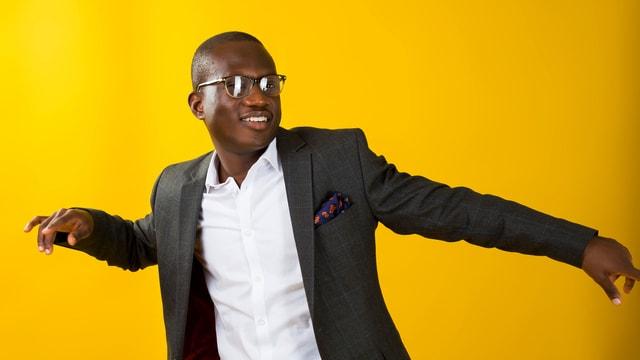 Ein schwarzer Mann im Anzug vor gelbem Hintergrund, tanzend.