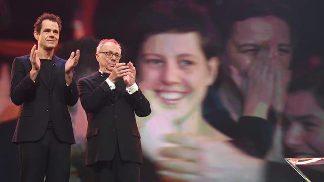 Zwei Personen auf der Bühne stehend.