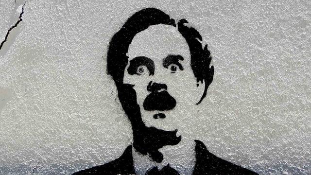 Schablonen Graffiti auf einer grauen Hauswand.