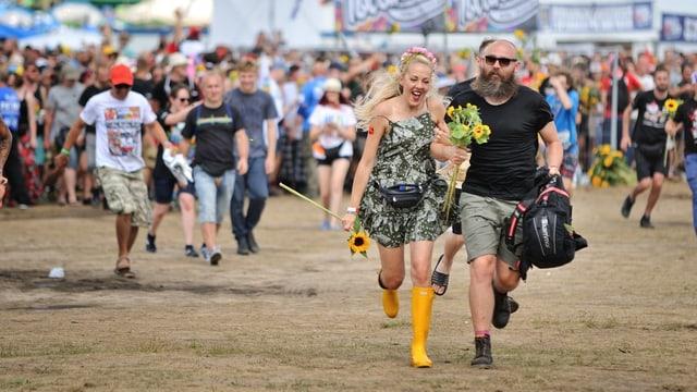 Leute rennen auf einem Festivalgelände.