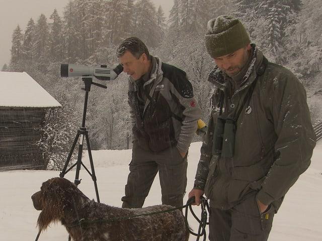 Die Wildhüter Flütsch und Gujan überwachen die Sonderjäger mit einem Fernglas.