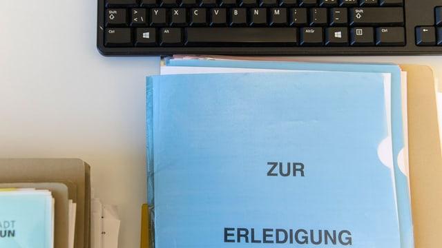 Dossier und Computertastatur