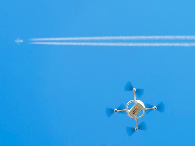 Drohne vor Kondensstreifen eines Jets.