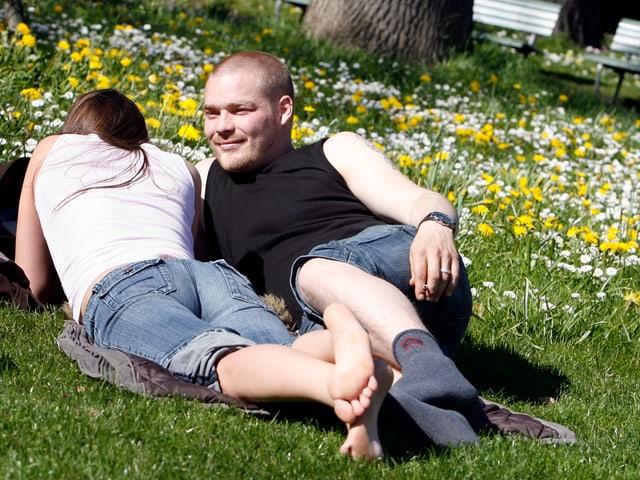 Ein junges Paar sonnt sich nahe beieinander auf einer Wieso mit Frühlingsblumen.